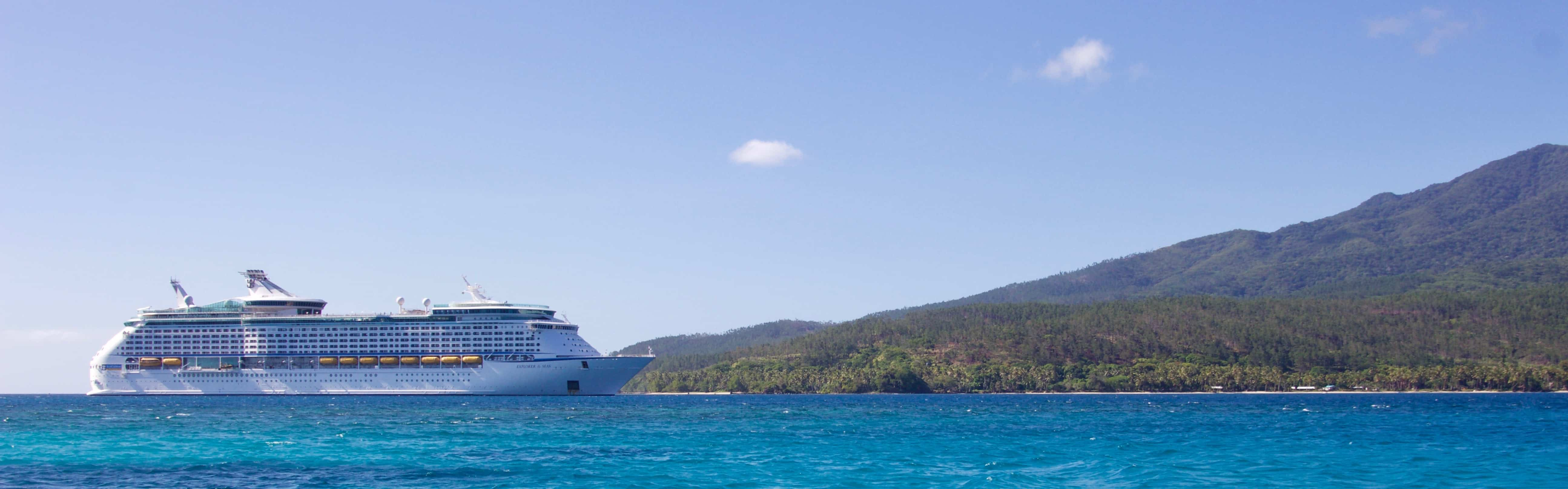 Ocean cruise liner with blue sky and hills behind it